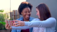 Two friends sat outside at early evening taking selfies video