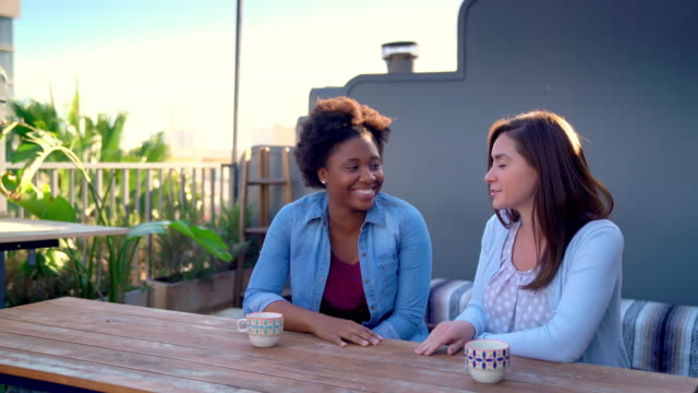 Two friends sat outside at early evening talking video