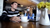Two friends sitting in cafe, talking, drinking coffee and using laptop video