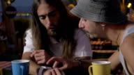 Two friends using smartwatch in street cafe video