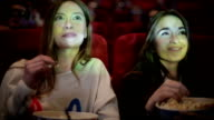 two friends watching movie in cinema video