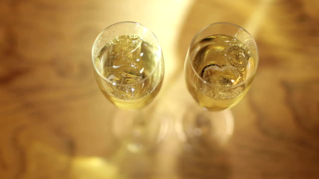Two full glasses of champagne with ice cubes. video
