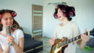 Two funny girls singing with comb and playing electric guitar dance, sing and have joy at home video
