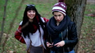 Two funny looking girlfriends posing by a tree in a park on a sunny autumn day video