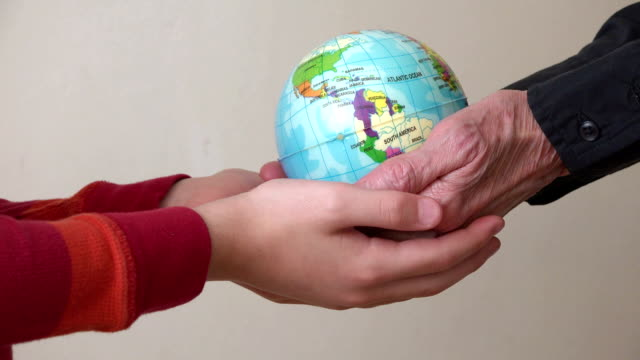 Two generation hands holding a globe, environmental concept video