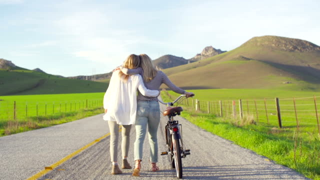 Two Girl Best Friends Walking Down Country Road With Bike At Sunset video
