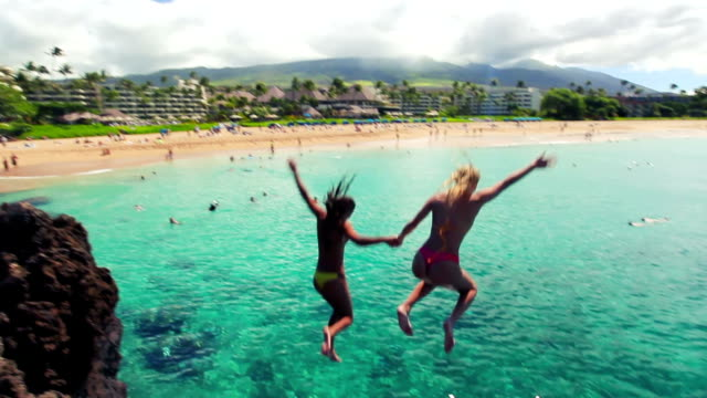 Two Girl Friends Jump Off Cliff H into Ocean in Bikinis in Hawaii. video