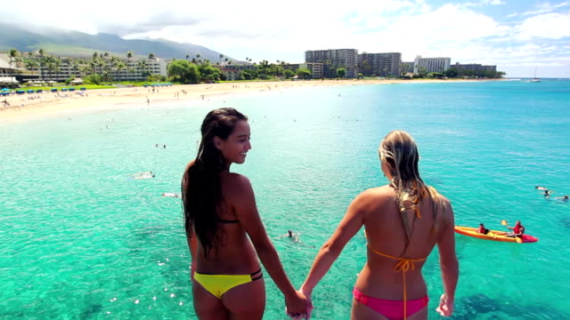 Two Girl Friends Jump Off Cliff Holding Hands into Ocean in Bikinis in Hawaii. video