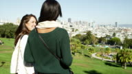 Two girl friends stand on top of a hill in a park on a sunny day and take pictures of the city below them with a tablet, medium shot video
