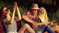Two girl with funny boy rejoicing with guitar in the sunny park. Slow motion video