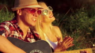 Two girl with funny boy rejoicing with guitar in the sunny park video
