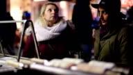 Two girlfriends buying trdelnik on street kiosk video