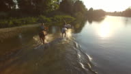 CLOSE UP: Two girlfriends hanging out and riding horses in river at sunny day video
