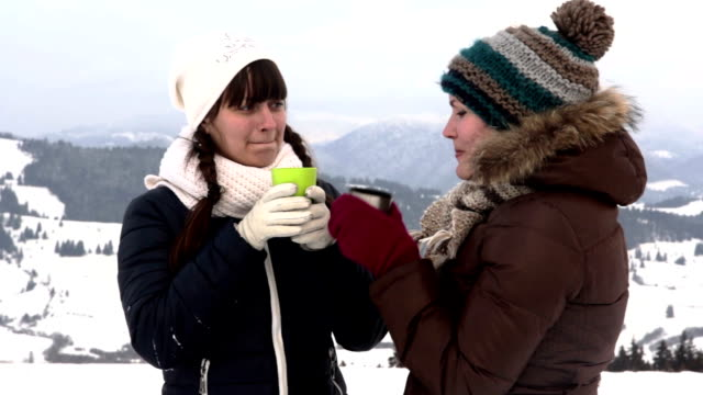 Two girlfriends have tea in mountains video