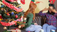 Two girlfriends opening Christmas gifts on Christmas Eve video