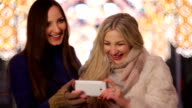 Two girls, a brunette and a blonde doing a selfie on the background of bright festive city lights. video