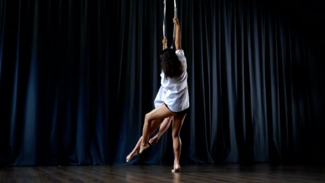 Two girls are circling on the aerial hoop and performs a gymnastic trick video