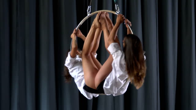 Two girls are spinning in the aerial hoop video