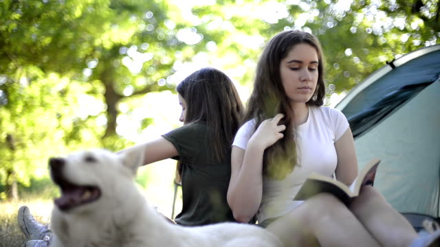 Two girls camping with her dog video