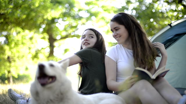 Two girls camping with her dog,one girl reading a book. video