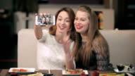 Two girls doing various selfie in the restaurant. video