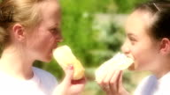 Two girls eating doughnuts video
