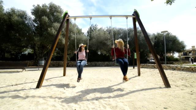 two girls enjoying swing in the park video