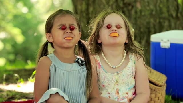 Two girls have fun eating fruit video