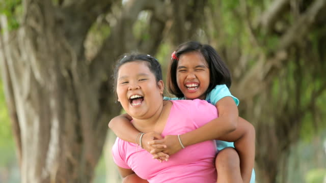 Two girls having fun take the other a piggyback video