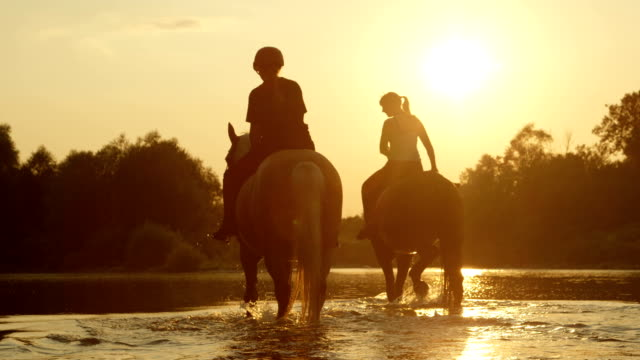 CLOSE UP: Two girls horseback riding horses along the river at magical sunset video