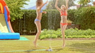 SLO MO Two girls jumping around water sprinkler video