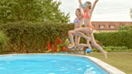 SLO MO TS Two girls jumping into pool together video