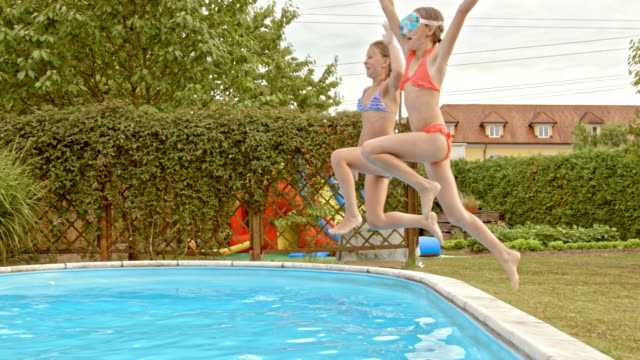 SLO MO TS Two girls jumping into the pool together video