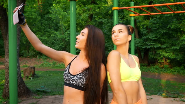 Two girls make merry fitness selfie. Sports figures and good mood video
