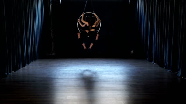 Two girls performs a trick in the aerial hoop video