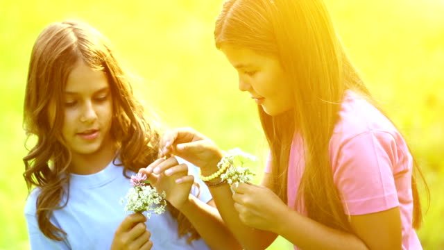 Two girls picking flowers outdoors. video