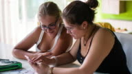 Two girls posting on the Social network at mobile phone video