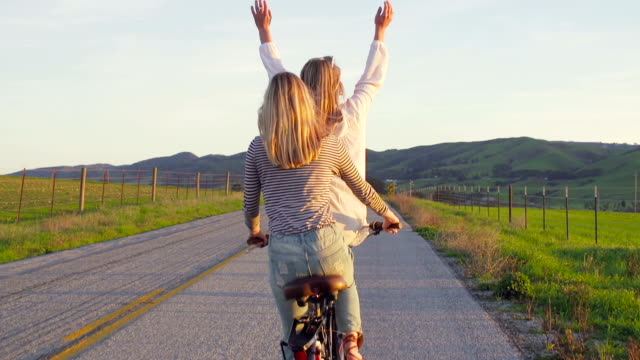Two Girls Riding Bike At Sunset With Hands Up In Air video