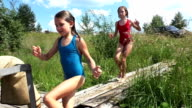Two girls run and jump from the pier into the water. video