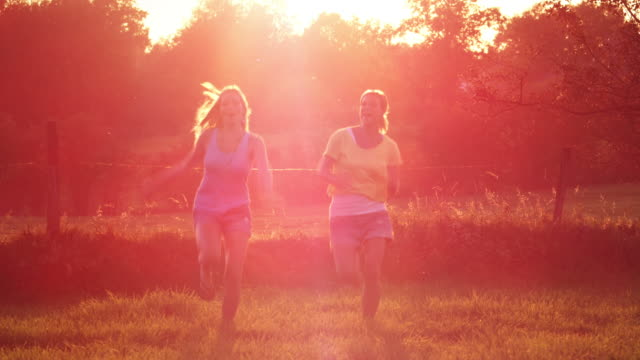 Two girls running over meadow video