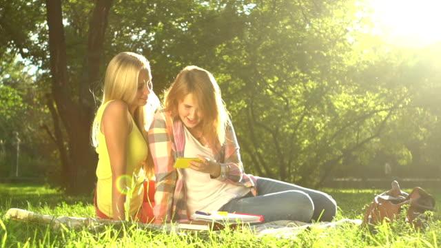 Two girls taking Selfie on green lawn video