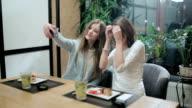 Two girls taking selfies in japanese restaurant video