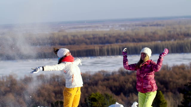 Two girls throw snow. Slow motion. video