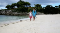 Two girls walking on a tropical beach video