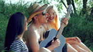 Two girls with funny boy resting on the grass and playing the guitar video