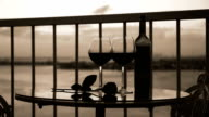 Two glasses and bottle with red wine on balcony video