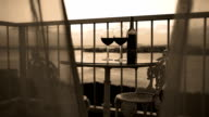 Two glasses and bottle with red wine on balcony with blowing curtains at sunset video