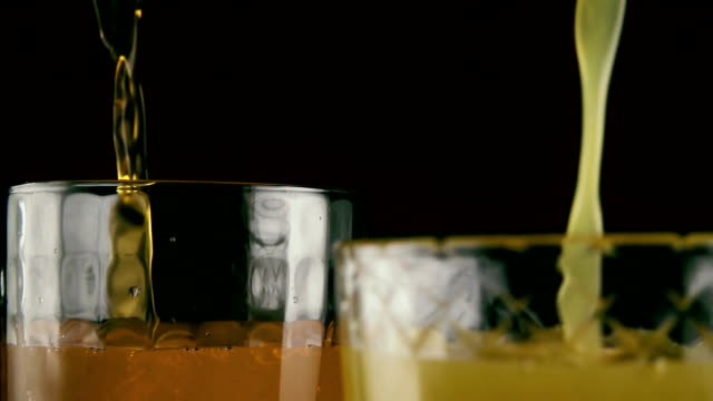 Two glasses full of juice and soda. Slow motion video