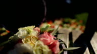 Two Gold Wedding Ring in infinity sign in the open piala lying on the lush colorful flower petals. Love concept video
