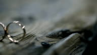 two golden rings on photo shoot on wooden table outdoors on wedding video